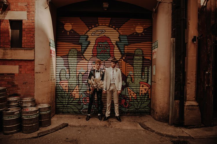 Two grooms standing in front of a shutter covered in graphic art