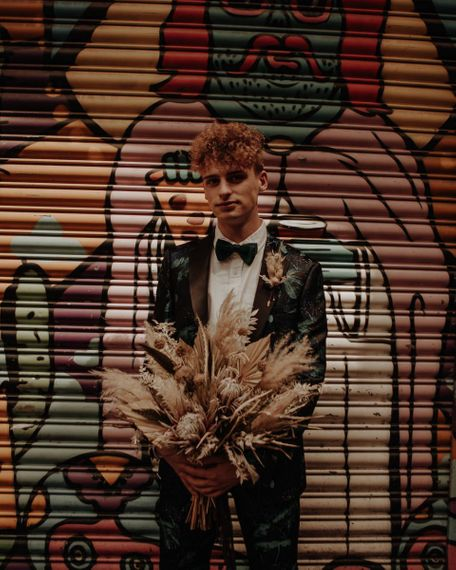 Stylish groom in patterned suit holding a dried flower wedding bouquet