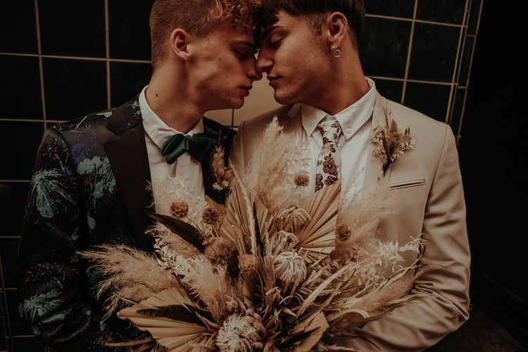 Grooms embracing in patterned and beige suits holding a bouquet with dried grasses and flowers