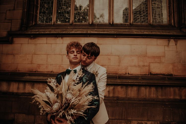Groom in beige suit embracing his husband at a Manchester elopement