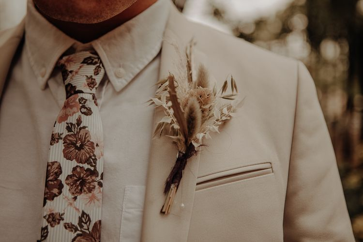 Patterned tie, beige suit and dried flower buttonhole