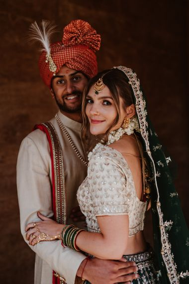 Groom in red and gold Indian wedding suit