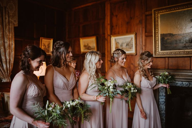 Bridesmaids in blush pink dresses with green bouquets