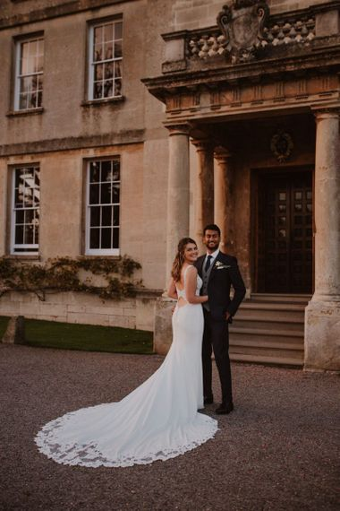 Bride in Maggie Sottero Kelset wedding dress with lace edge long train