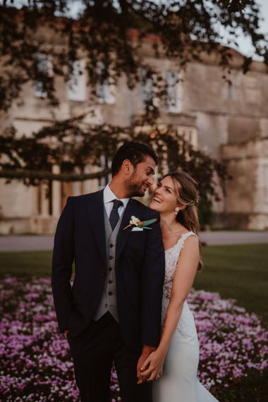 Groom in three-piece suit and bride in Maggie Sottero wedding dress