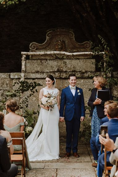 Wedding Ceremony   Bride in Lace Back Pronovias Wedding Dress   Groom in Hawes and Curtis Navy Suit & Bow Tie   Outdoor Cornish Wedding at Boconnoc Estate   Nick Walker Photography