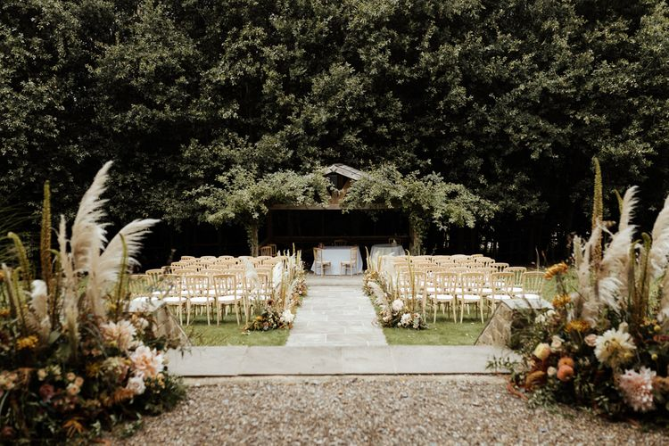 Outdoor wedding ceremony at Bury Court Barn with boho flowers