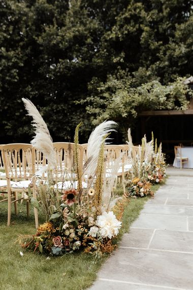 Aisle flower decor with pampas grass, foliage and dahlias