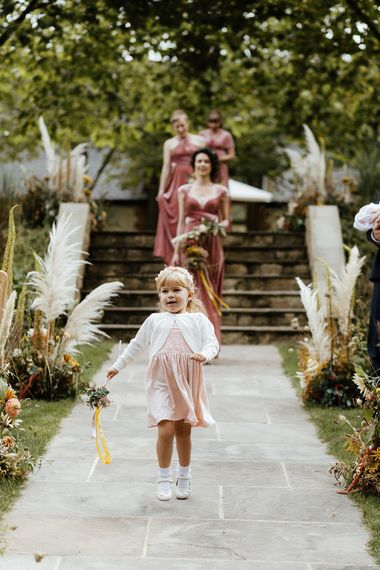 Flower girl walking down the aisle in a pink dress and white cardigan