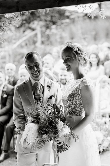 Black and white portrait of the bride and groom exchanging vows