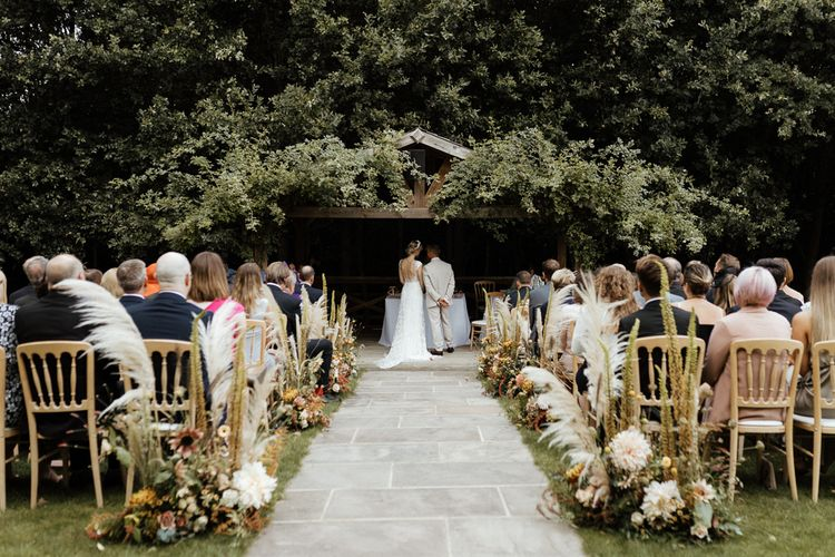 Outdoor wedding ceremony at Bury Court Barns with bride in Rime Arodaky dress