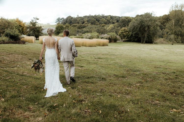 Bride in Rime Arodaky wedding dress and groom in stone suit walking through the fields