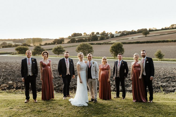 Wedding party portrait with the bride in a Rime Arodaky gown, bridesmaids in pink velvet dresses and groomsmen in  black and stone suits
