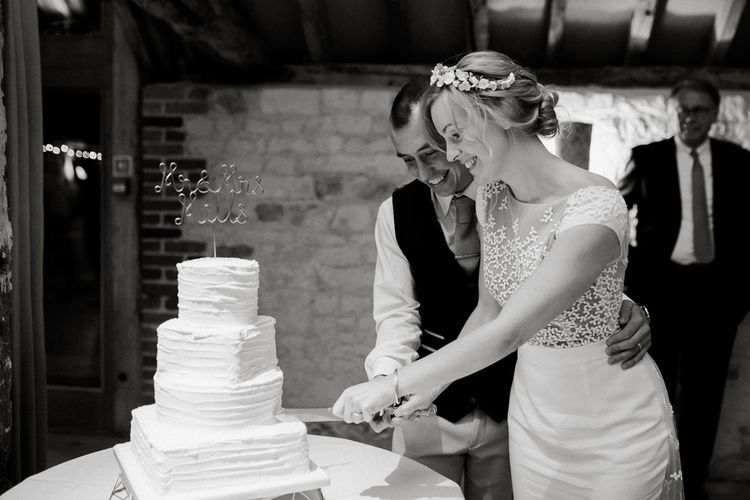 Bride and groom cutting the buttercream wedding cake