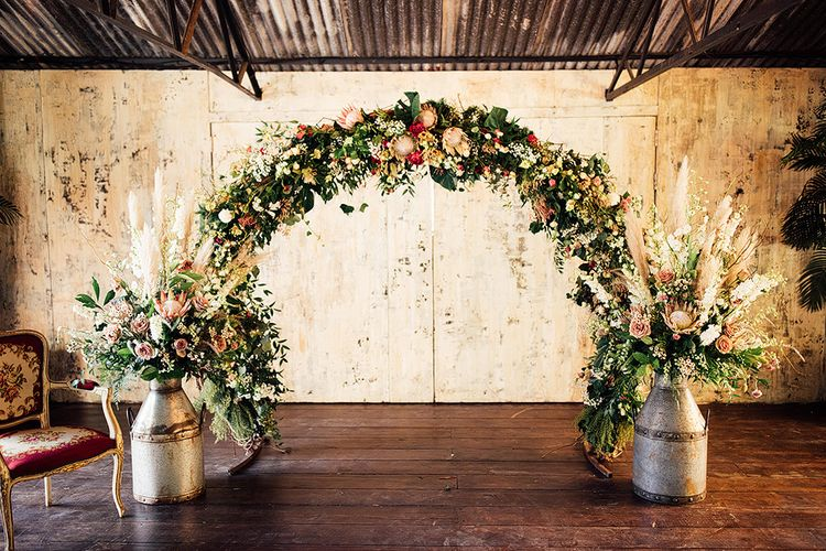 Floral Arch and Milk Churn Arrangements with King Proteas, Roses and Pampas Grass