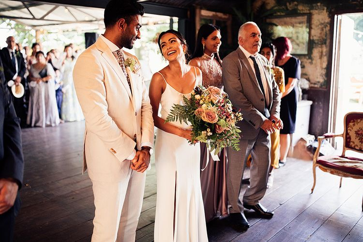 Bride in Belle & Bunty Wedding Dress Meeting Her Groom at the Altar in a White Suit