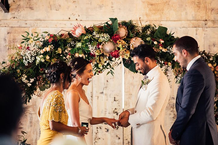 Bride and Groom Exchanging Rings During the Wedding Ceremony Under a King Protea Floral Arch