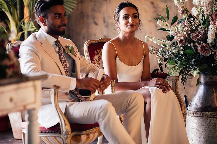 Stylish Bride and Groom Sitting on Chairs During the Wedding Ceremony