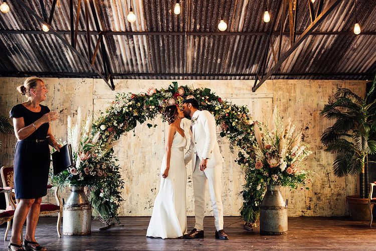 Bride in Belle & Bunty Wedding Dress and Groom in Cream Suit Kissing in Front of a King Protea Floral Arch