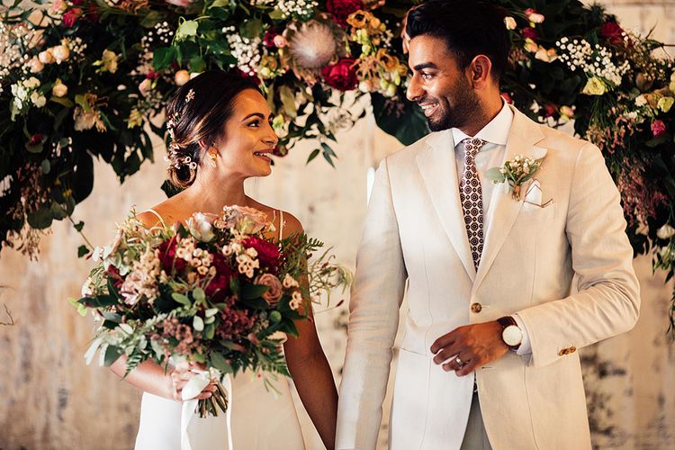 Bride in Belle & Bunty Wedding Dress and Groom in Cream Suit Smiling in Front of a King Protea Floral Arch