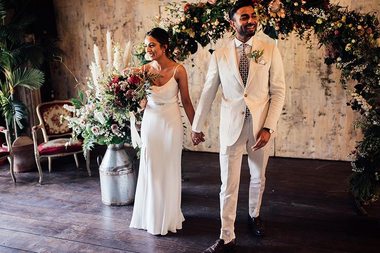 Bride in Belle & Bunty Wedding Dress with Front Split and Groom in Cream Suit Holding Hands in Front of a King Protea Floral Arch