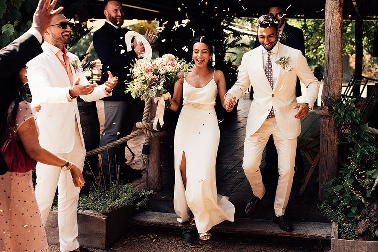 Confetti Exit with Bride in Belle & Bunty Wedding Dress with Front Split and Groom in Cream Suit