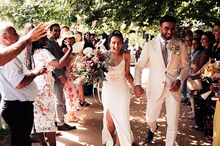 Confetti Moment with Bride in Belle & Bunty Wedding Dress with Front Split and Groom in Cream Suit