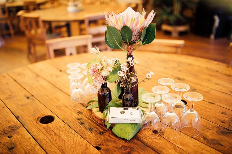 Brown Bottle Table Centrepieces filled with Pink Flower Stems and King Proteas