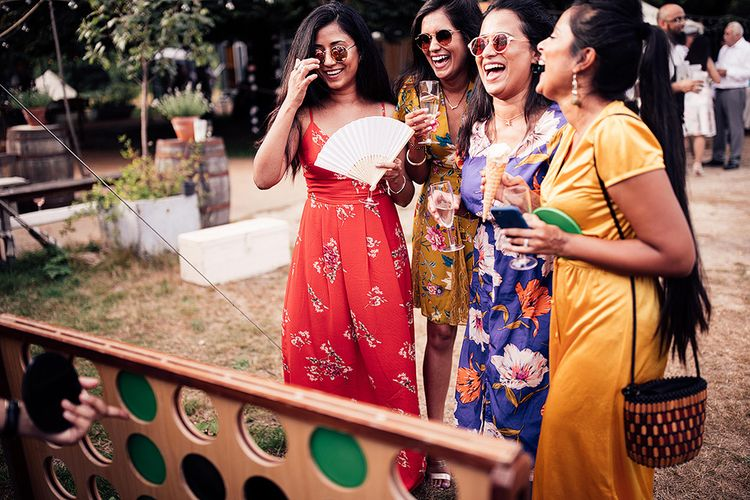 Stylish Wedding Guests in Floral Outfits Playing Giant Connect Four