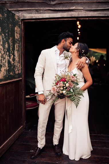 Groom in Cream Wedding Suit Kissing His Bride in a Minimalist Wedding Dress Holding a Pink and Green Bouquet