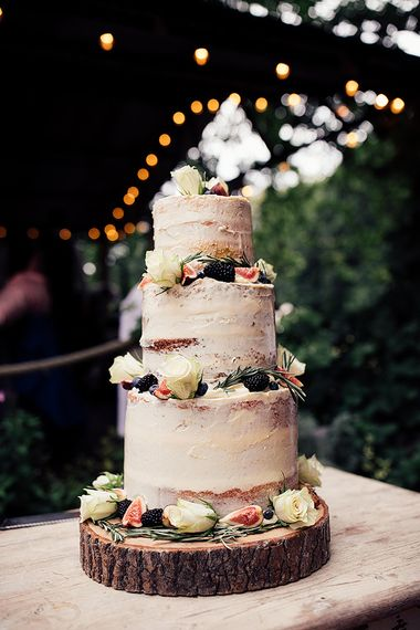 Semi Naked Wedding Cake Decorated with Flowers and Fruit on a Tree Slice Cake Stand
