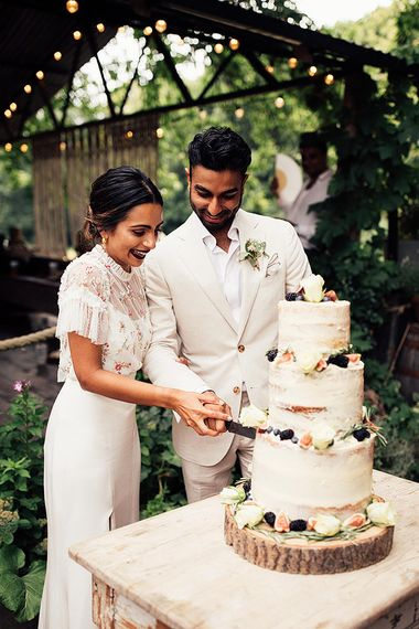 Bride in Belle & Bunty Wedding Dress and Embroidered Needle & Thread Top and Groom in Cream Wedding Suit Cutting the Semi Naked Wedding Cake