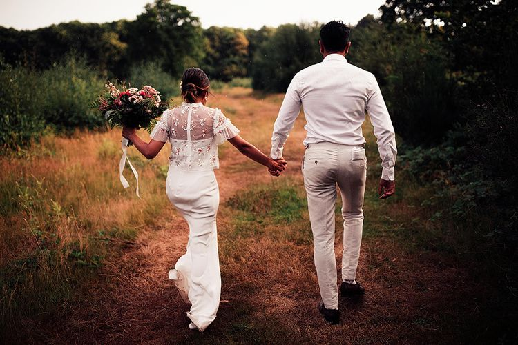 Bride in Belle & Bunty Wedding Dress and Embroidered Needle & Thread Top and Groom in Cream Wedding Suit Walking Through Fields