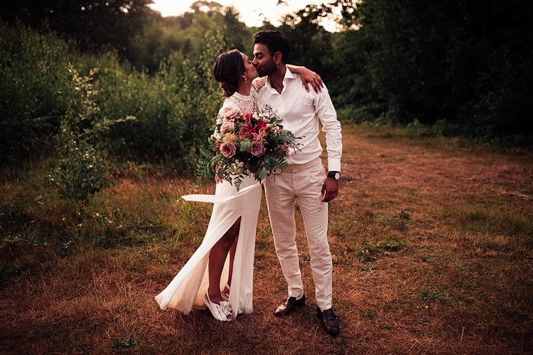 Bride in Belle & Bunty Wedding Dress and Embroidered Needle & Thread Top and Groom in Cream Wedding Suit Embracing in a Field