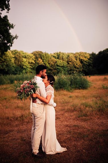 Bride in Belle & Bunty Wedding Dress and Embroidered Needle & Thread Top and Groom in Cream Wedding Suit Embracing Under a Rainbow