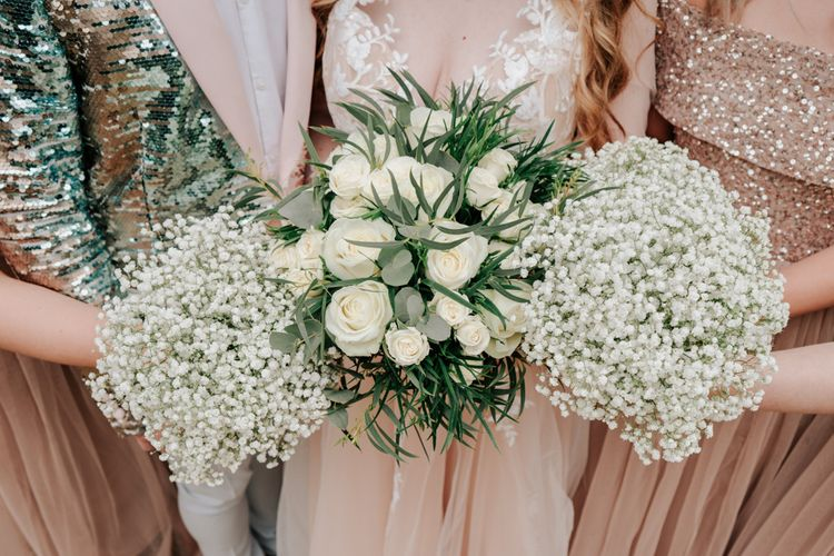 White Wedding Flowers Against Pink Wedding Dress and Bridesmaid Dresses