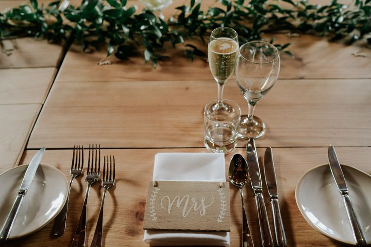 Wedding Table Place Setting With Foliage and White Flowers