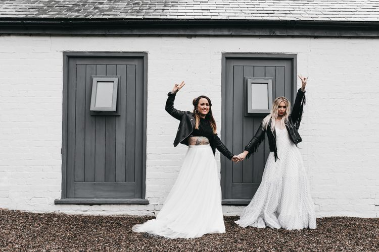 Same-sex brides in a back and white dress, separates and leather jackets