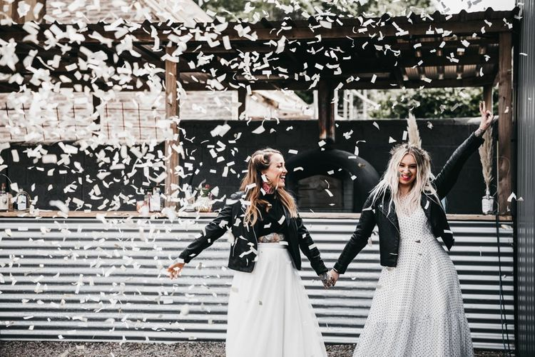 Confetti cannon moment with brides in black and white dress and separates