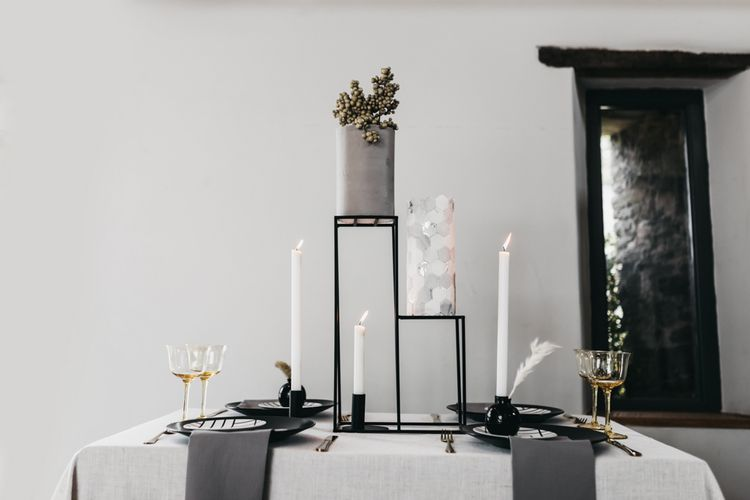 Intimate black and white table decor with wedding cake centrepiece