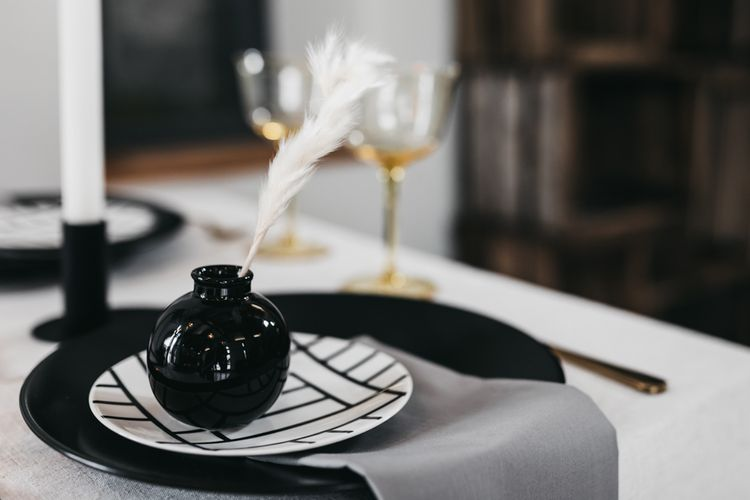 Place setting with monochrome tableware and white feather decor