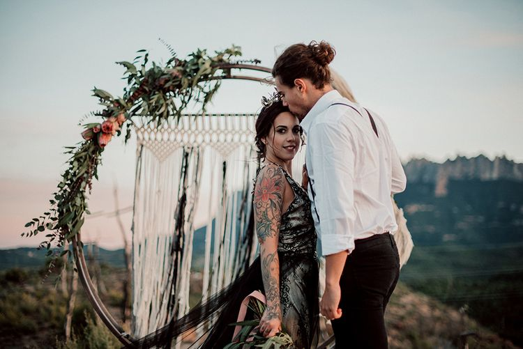 Bride in Antonia Serena Atelier Wedding Dress with Groom Standing in Front of Steel Moon Gate Decorated with Macrame, Red Flowers, Foliage and Pampas Grass