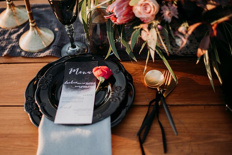 Place Setting with Black Tableware and Cutlery, Menu Card and Floral Centrepiece