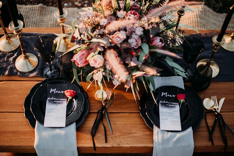 Table Place Settings with Black Tableware and Cutlery, Menu Cards and Deep Red Floral Centrepiece