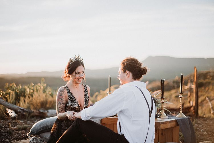Bride in Black Wedding Dress and Gold Crown Headdress Laughing with Her Groom in White Shirt and Braces