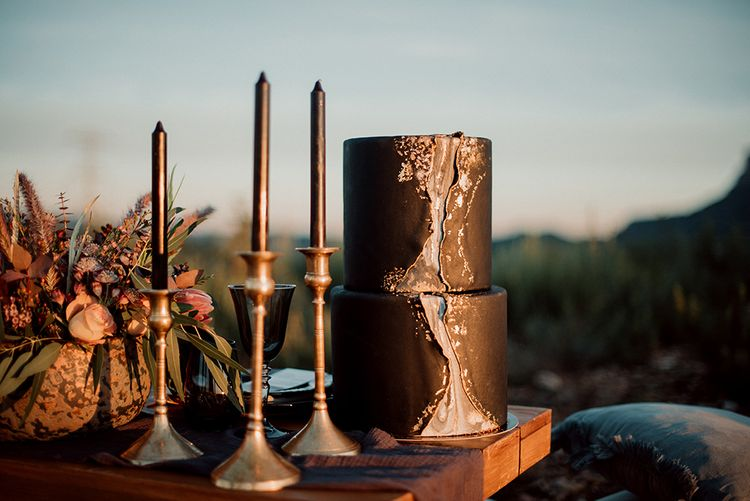 Black Wedding Cake with Front Marble Detail Next to Candlestick Decor