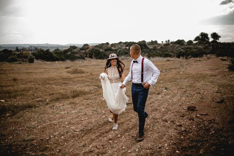 Bohemian bride and groom running through the fields