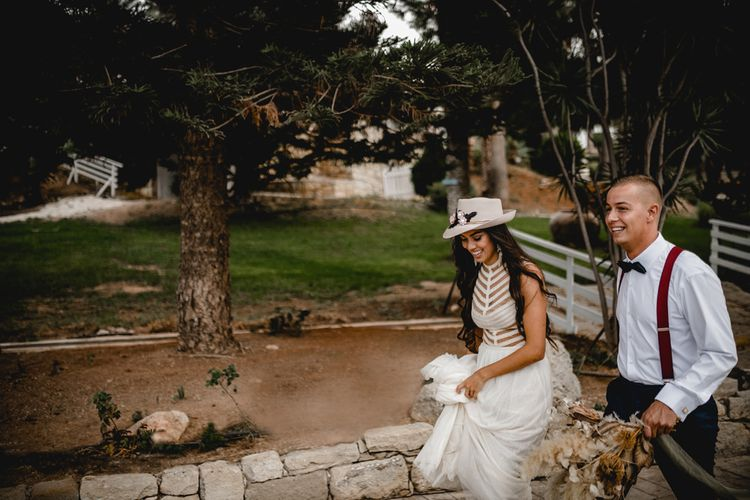 Boho bride and groom in bridal hat and braces