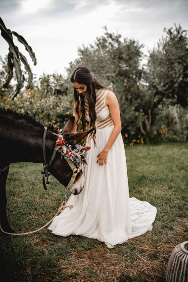 Bohemian bride with long hair petting a donkey