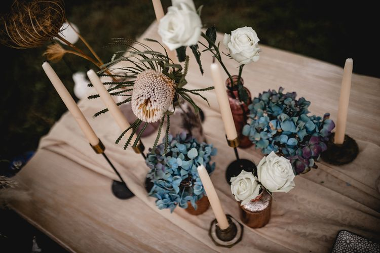 Taper candles and flowers stems in bottles